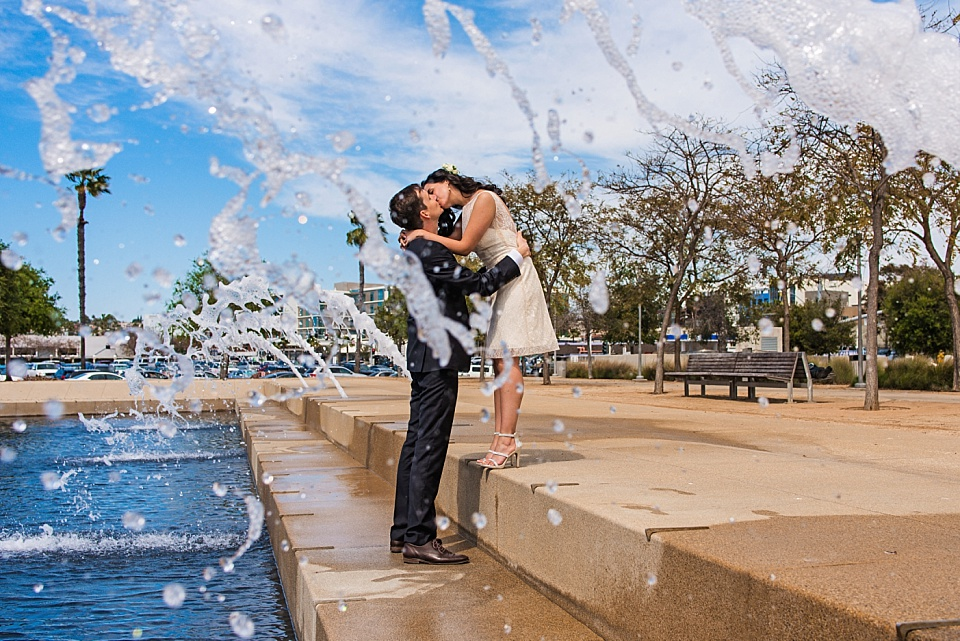 newlyweds kissing under fountains san diego courthouse wedding photographer