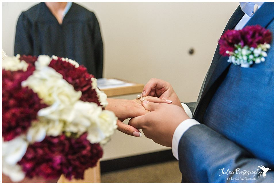 groom-placing-ring-on-brides-finger-san-diego-courthouse-downtown