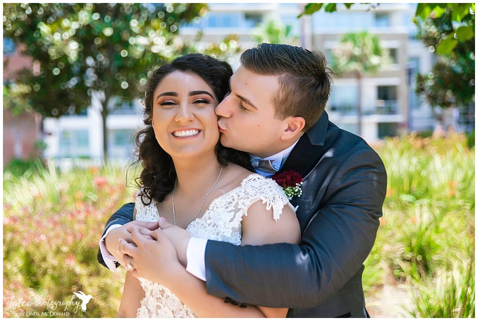 groom-kissing-bride-on-cheek-san-diego-courthouse-marriage