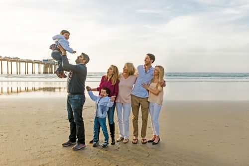 dad holding kid up in the air at the beach while family watches