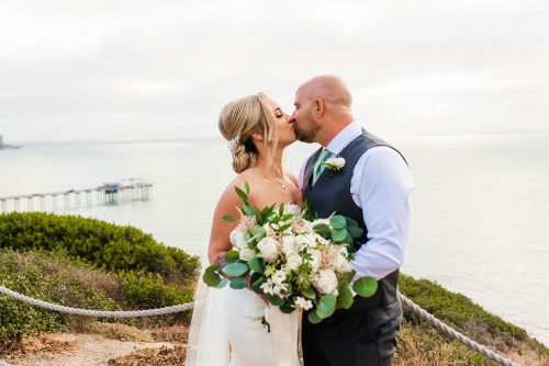portrait of bride and groom with la jolla scripps pier in the background