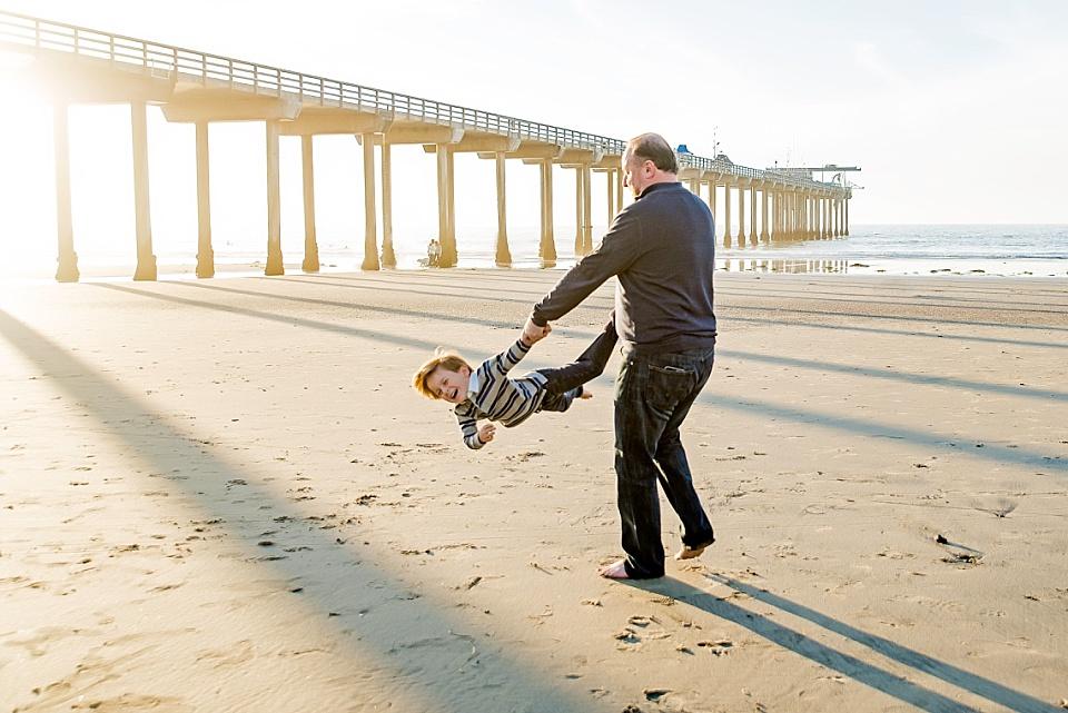 dad swinging boy around at scripps pier la jolla