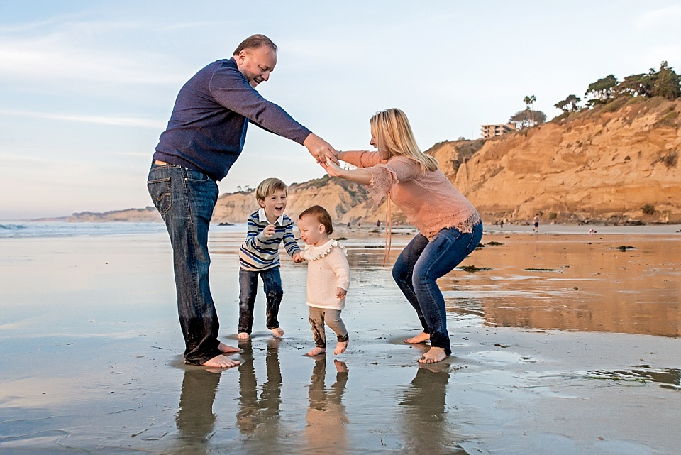 family playing together at photo session in la jolla beach
