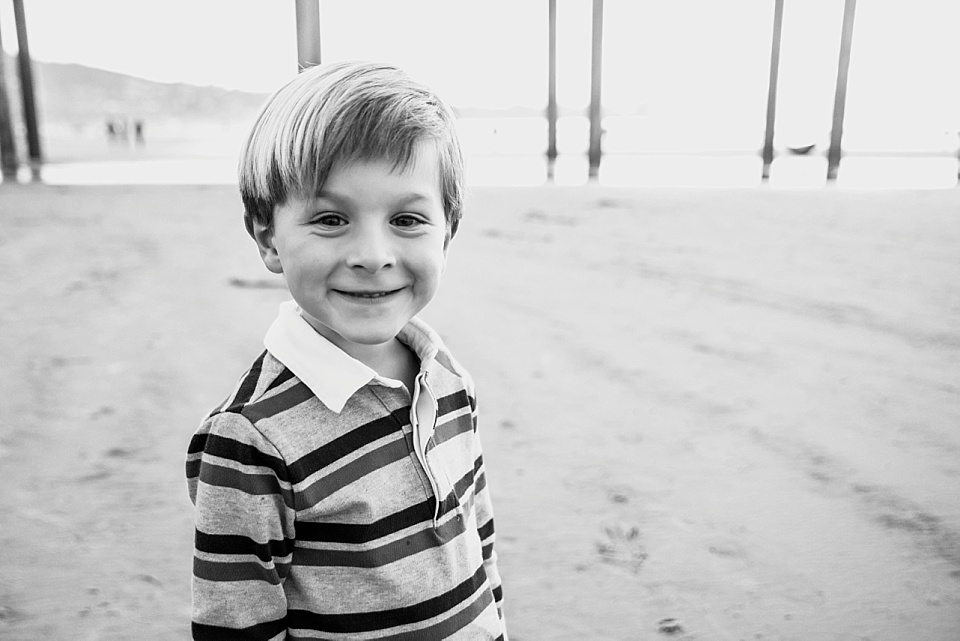 black and white portrait of little boy in front of scripps pier