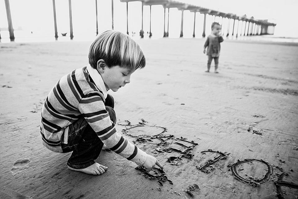 little boy writing in the sand in front of la jolla scripps pier
