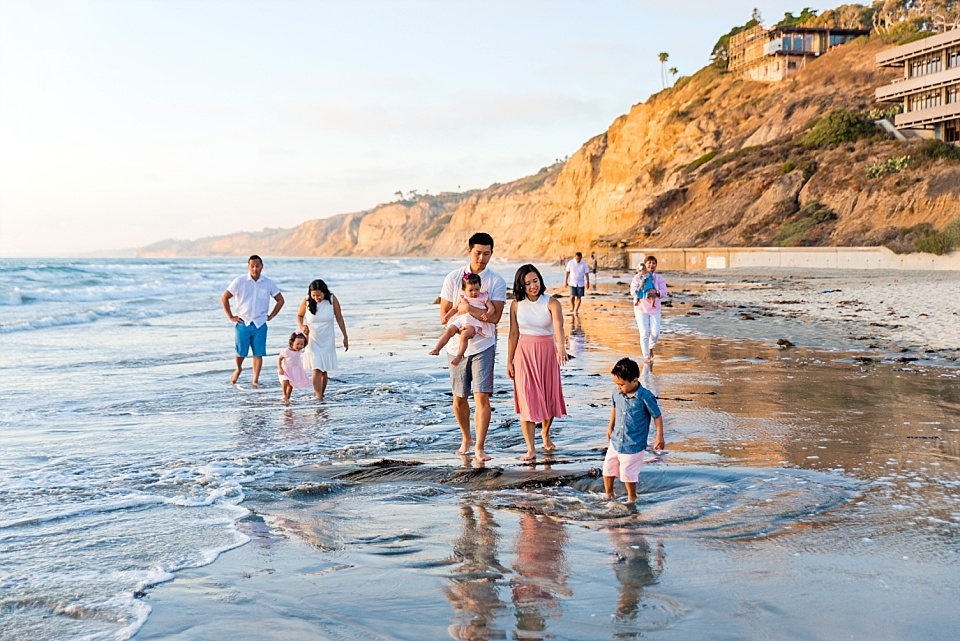 candid photo of family walking on san diego beach