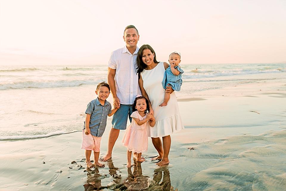 family of three posing for lifestyle photo on san diego beach