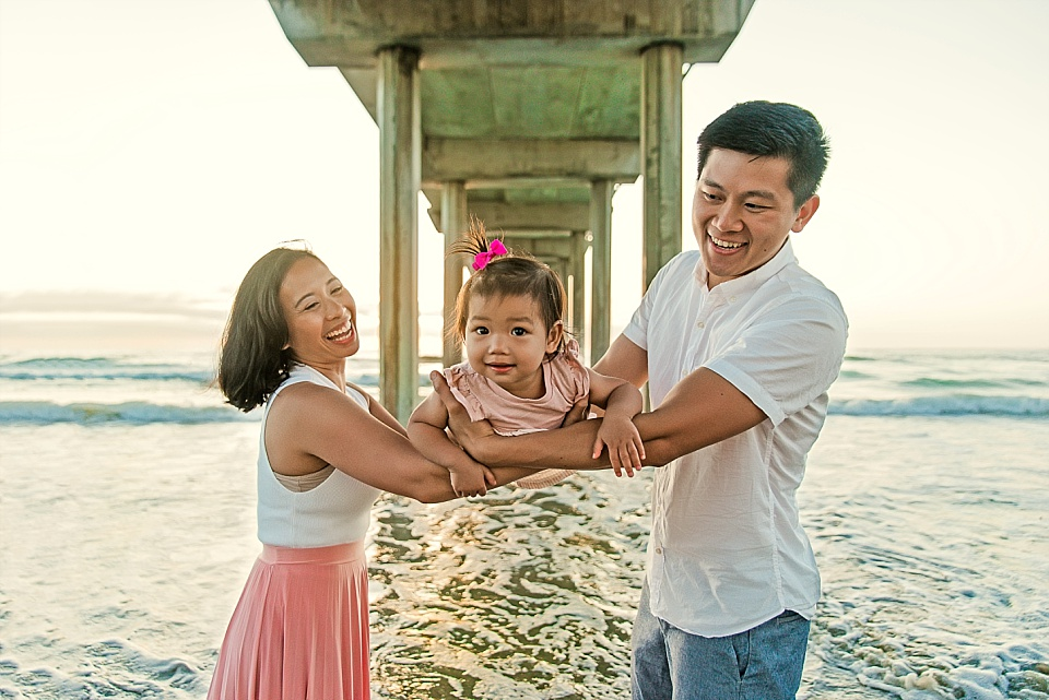playful family lifestyle pose underneath scripps pier La Jolla