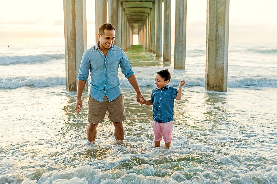 man and child playfully engaging underneath Scripps Pier La Jolla