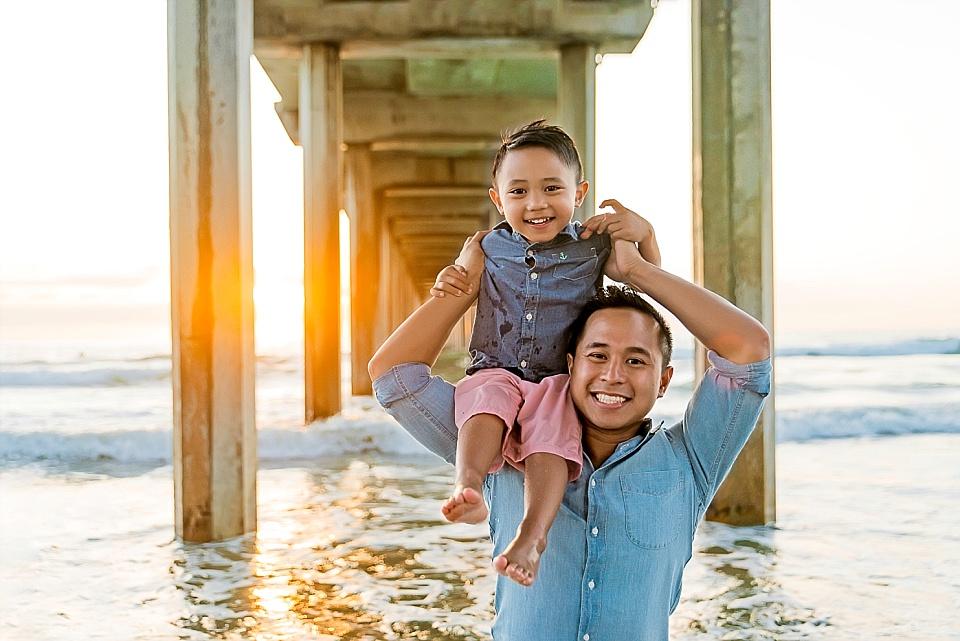 small child on mans shoulders posing underneath Scripps Pier La Jolla