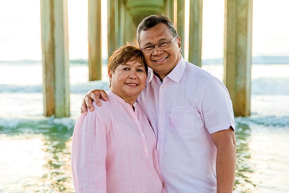 elderly couple posing underneath Scripps Pier La Jolla