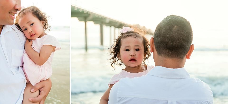 baby looking over dad's shoulder at scripps pier la jolla