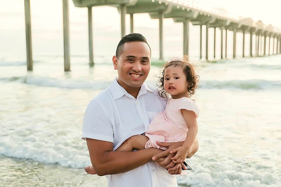 father holding baby girl in front of scripps pier la jolla