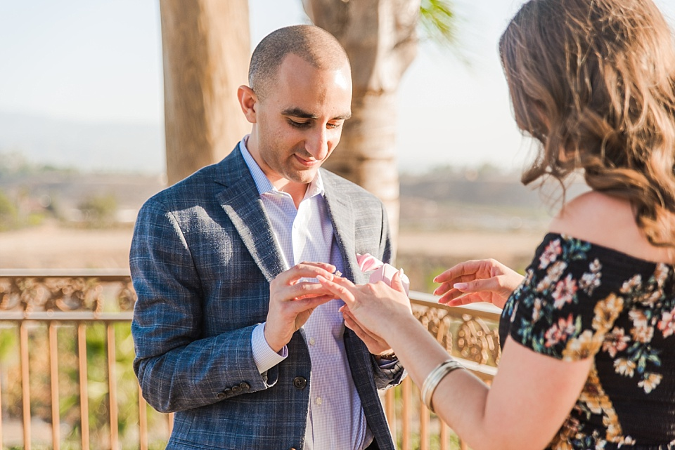 man placing ring on woman's finger for marriage proposal