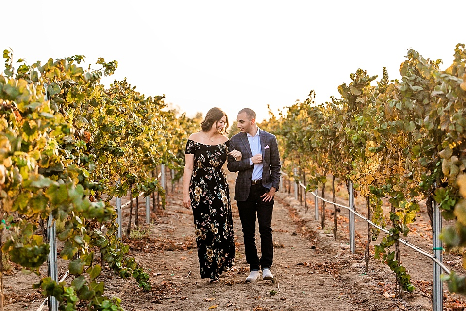 Carter Estate Winery engaged couple walking in vineyard