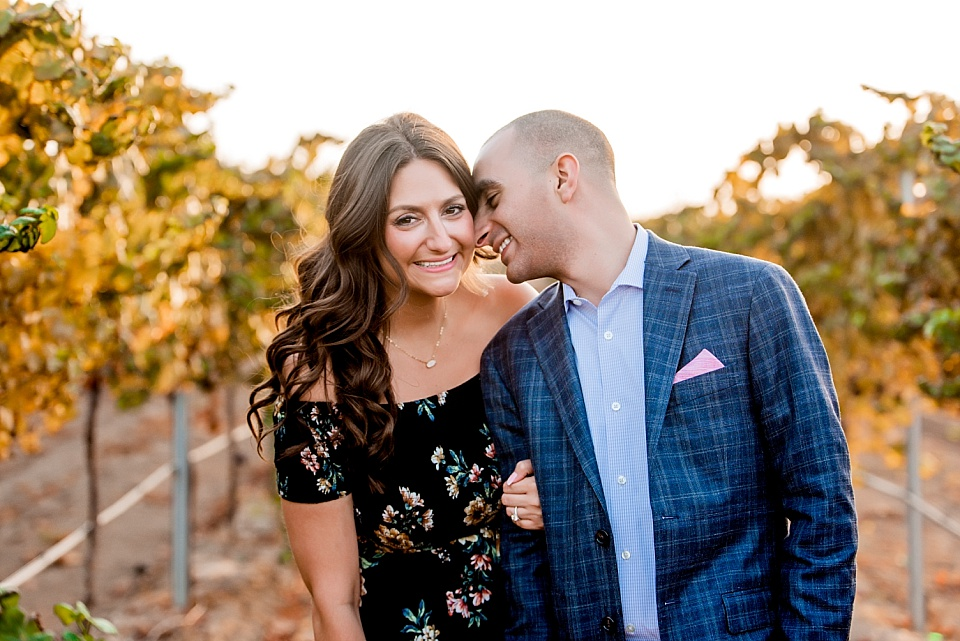 man nuzzling fiance in temecula vineyard