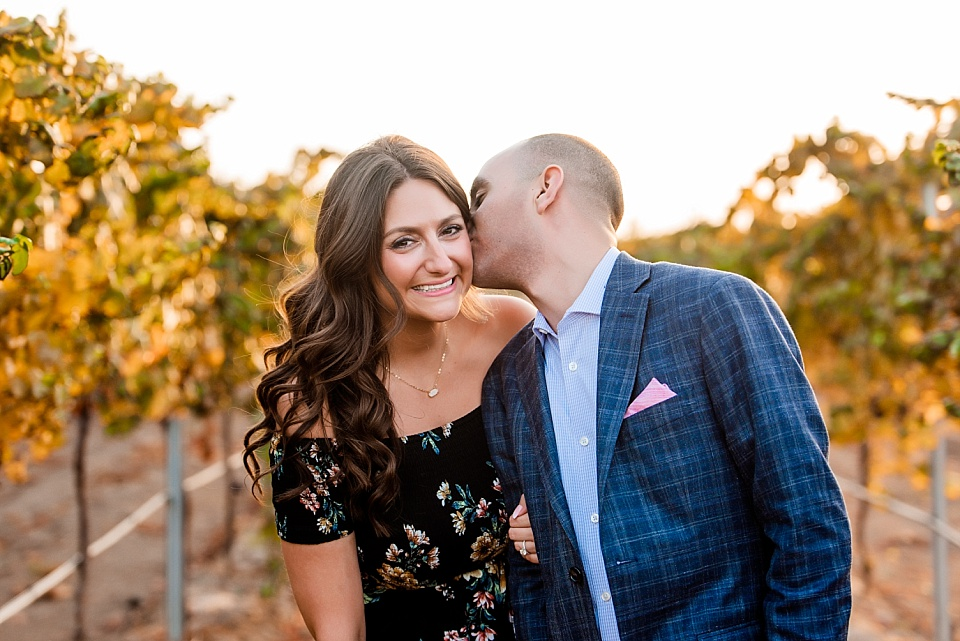 man kissing fiance at a temecula winery