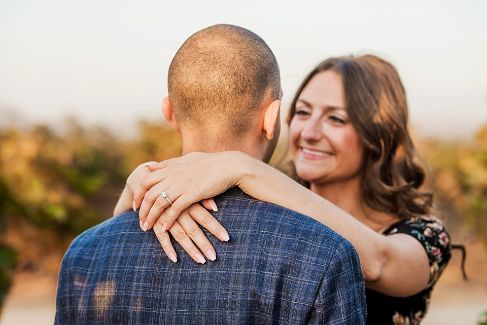 woman with arms around man show engagement ring