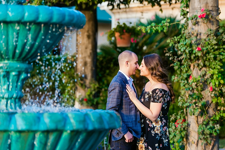 couple nuzzling behind a fountain at south coast winery temecula