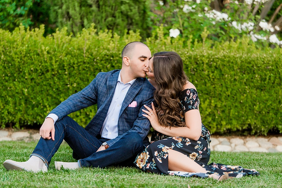 couple sitting on lawn kissing with Jalea Photography San Diego photographer