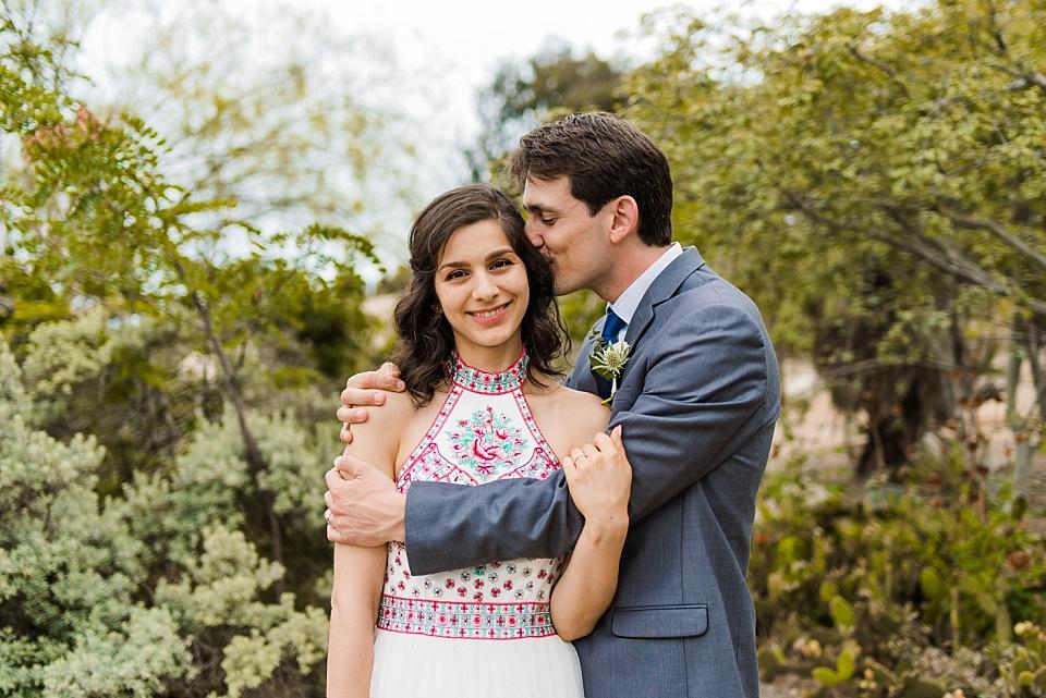 groom kissing bride old cactus garden balboa park