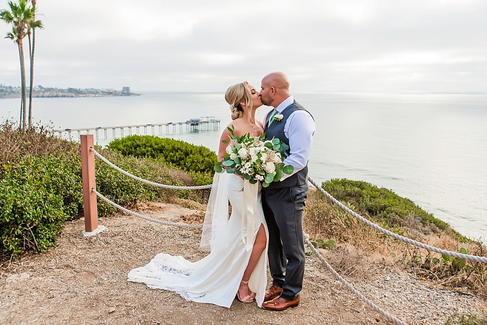 newlyweds kissing with scripps pier in the background la jolla wedding venues