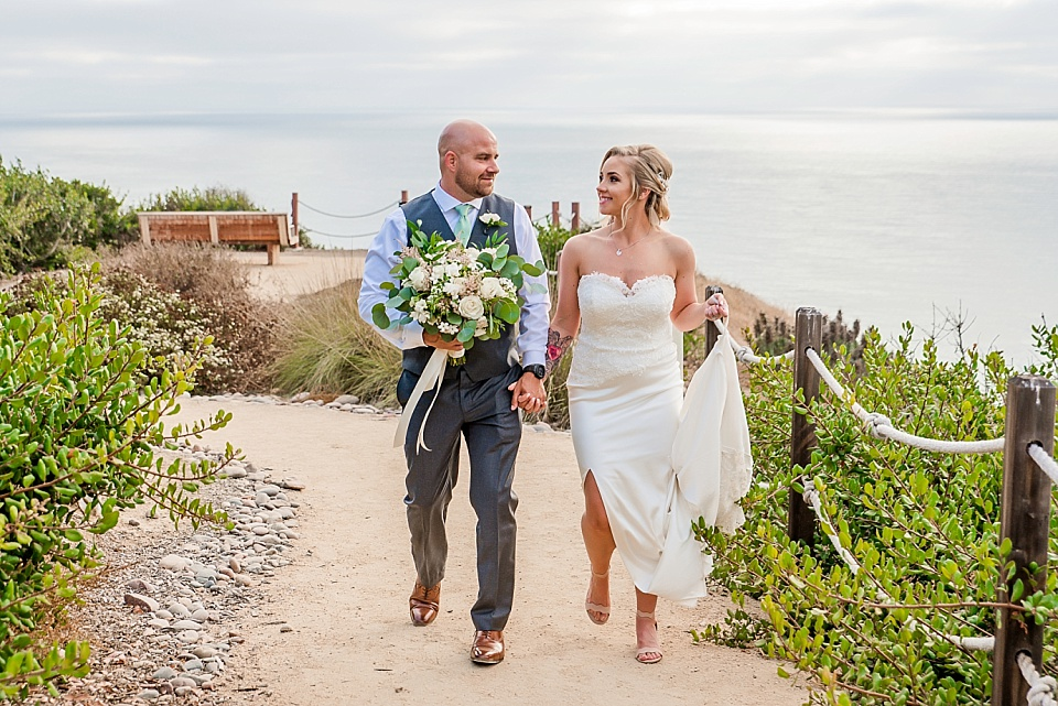 newlyweds walking on path la jolla wedding venues