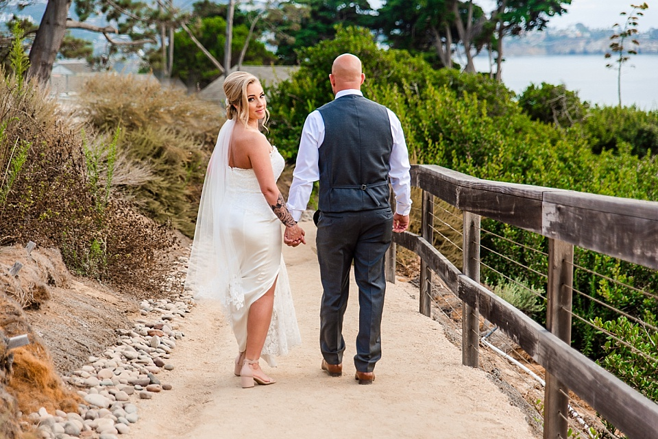 bride looking back while walking on path outdoor venues san diego