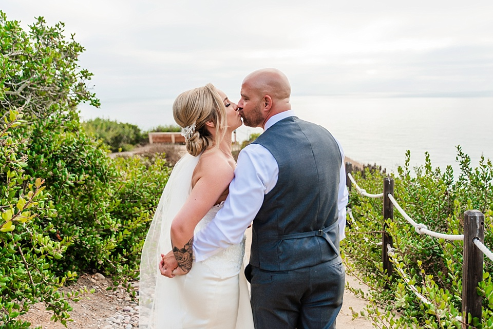 bride and groom kissing on path at martin johnson house