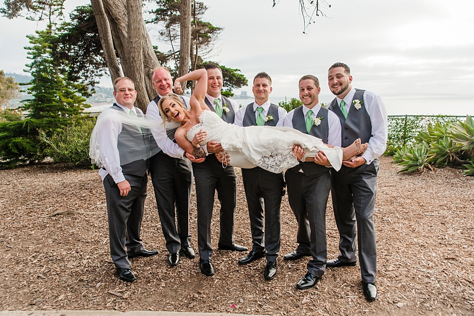 groosmen holding bride up at la jolla wedding venues