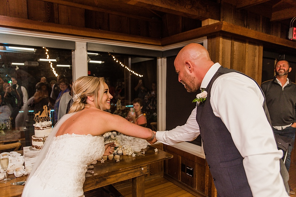 bride and groom being playful during cake cutting la jolla beach wedding venues