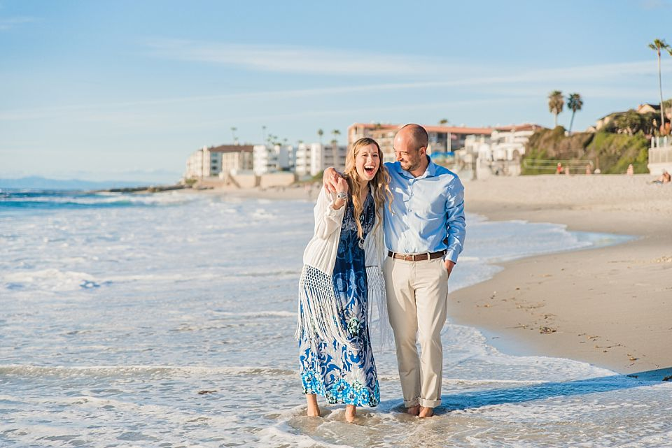 engaged couple walking in the water windandsea beach san diego engagement photoshoot