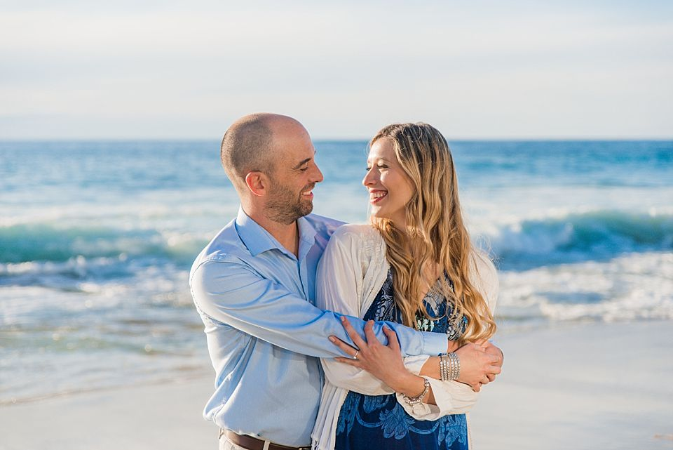 couple in an embrace at the beach la jolla engagement portraits