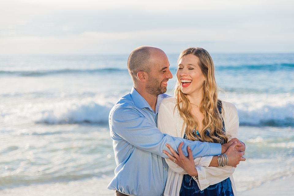 man woman laughing on the beach san diego enagagement session
