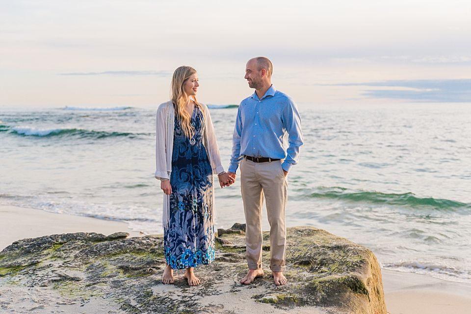 couple holding hands on beach rock san diego engagement photo inspiration