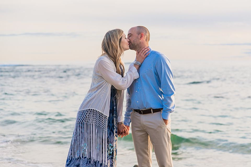 man and woman kissing at beach san diego engagement photographer