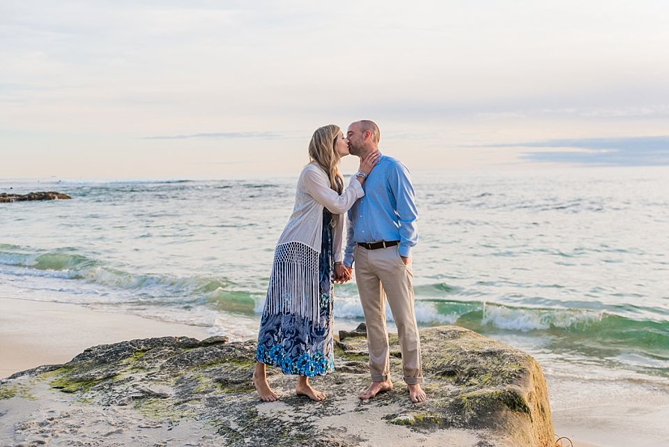 man woman kissing on rock windseabeach san diego engagement session