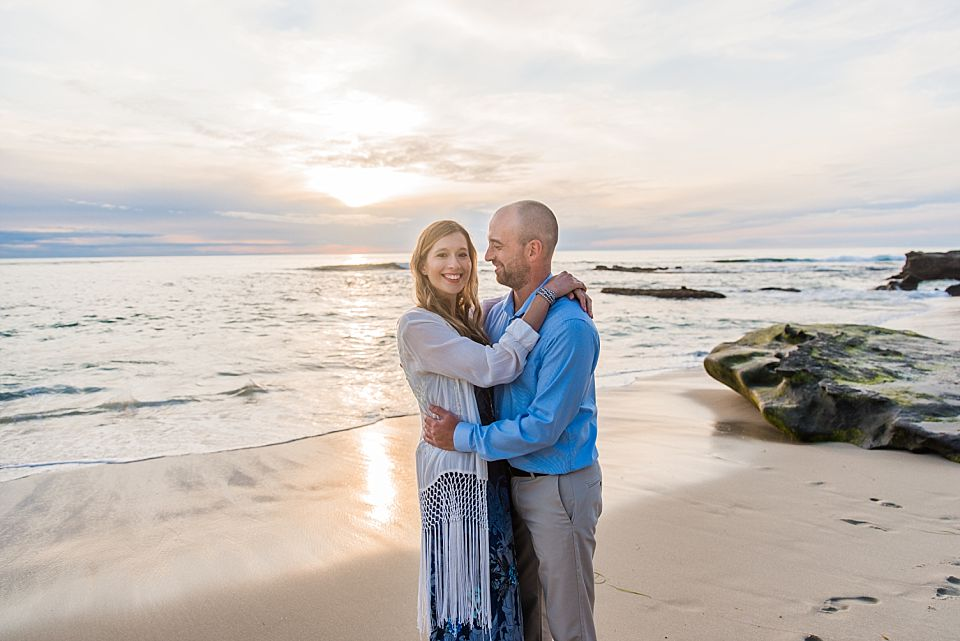 couple embracing engagement photos beach sunset san diego