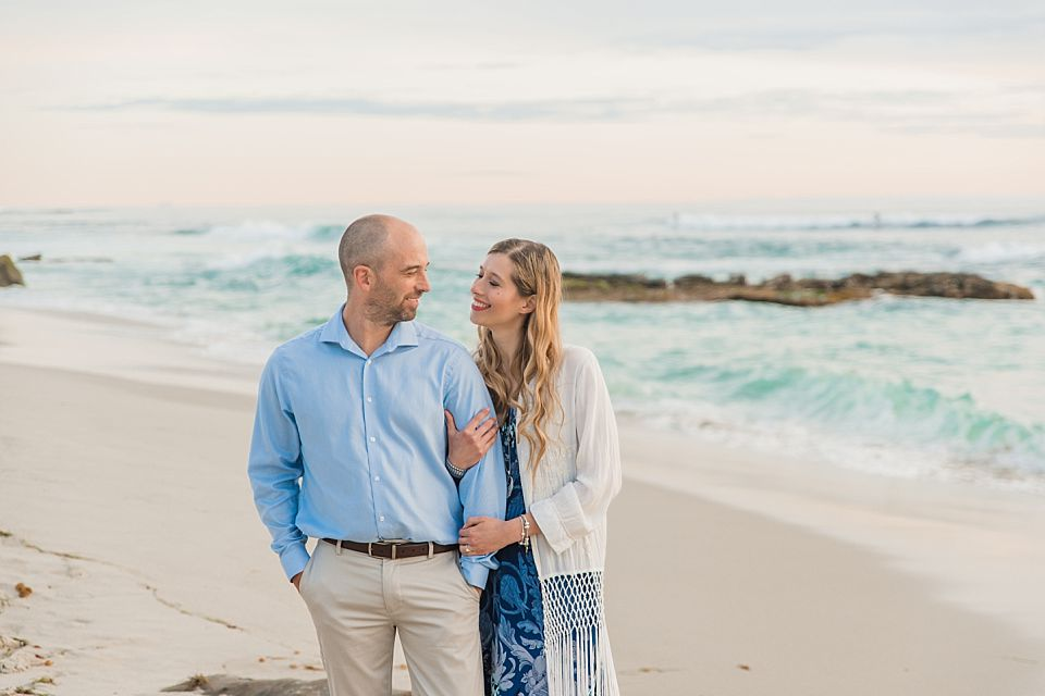 man woman smiling at each other on beach la jolla engagement photo ideas