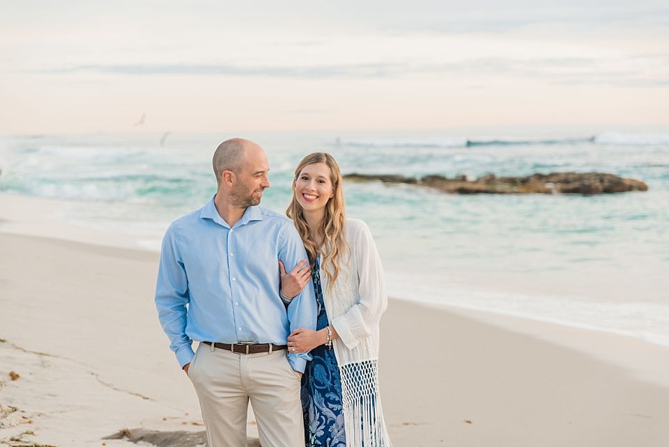 couple standing near ocean at sunset san diego engagement photographer