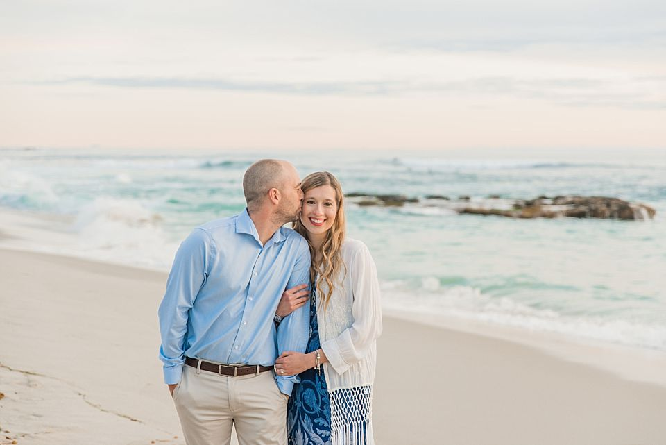 man kissing woman on cheek windandsea beach engagement photos