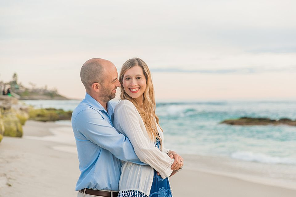 man woman standing on beach in embrace la jolla engagement portraits