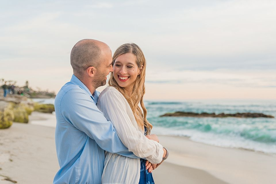 woman smiling at man while standing on beach san diego engagement photo inspiration