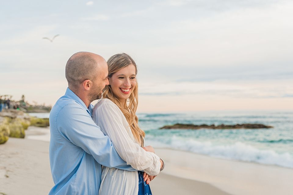couple embracing on beach la jolla engagement session