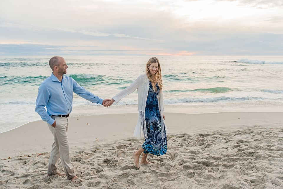 woman leading man on beach san diego engagement photographer