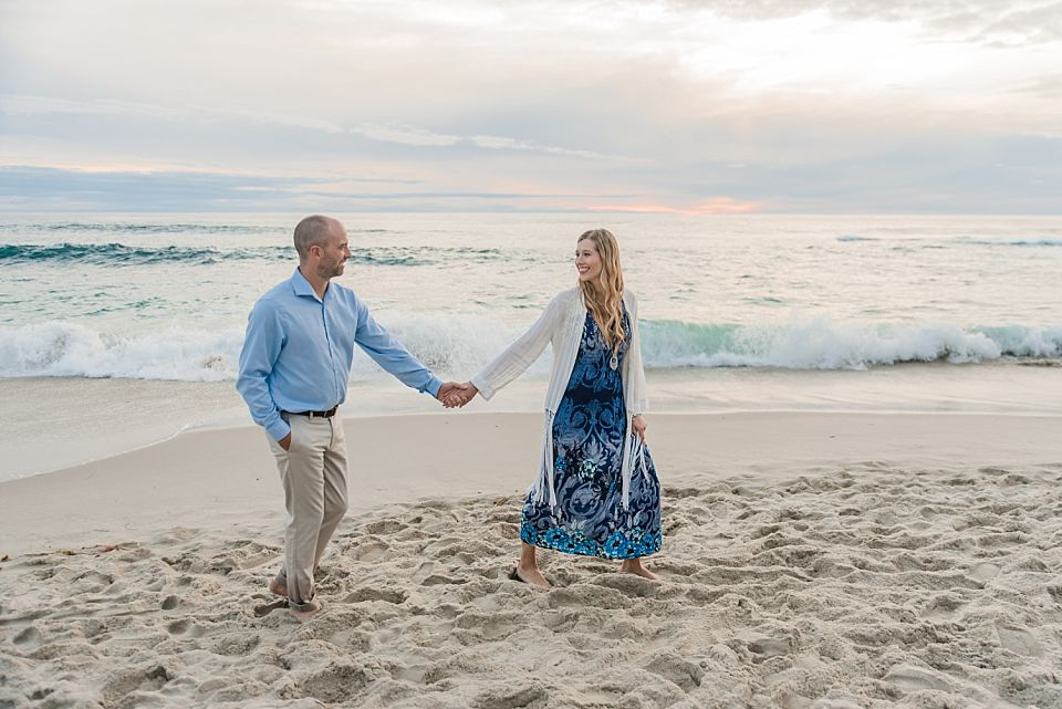 woman walking with man on beach san diego engagement photographer