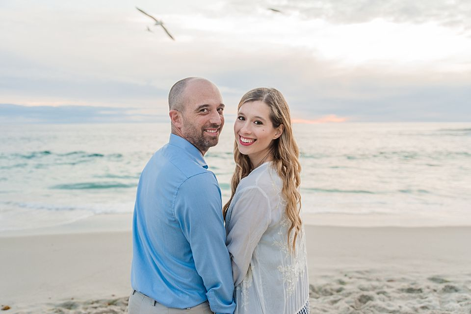 couple standing on beach smiling windandsea beach engagement photos