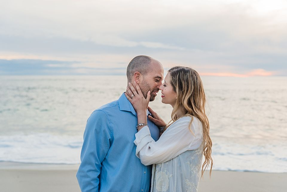 couple kissing at sunset on beach san diego engagement photos