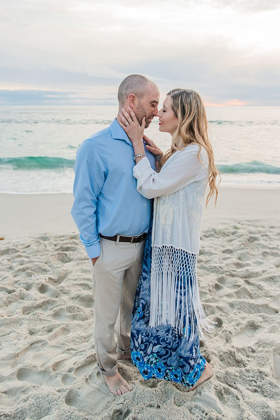 couple nuzzling on beach san diego engagement photographer