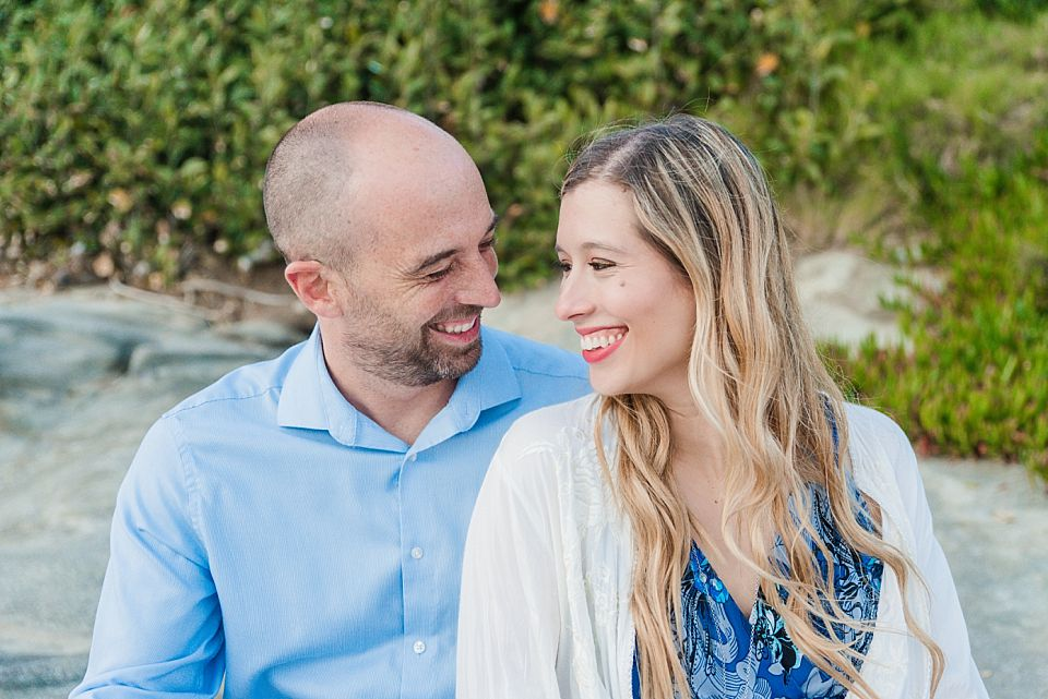couple sitting on rocks at beach san diego engagment photo ideas